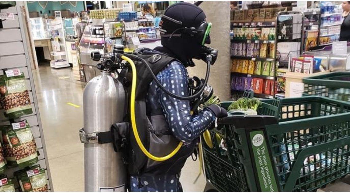 Homem veste equipamento de mergulho para ir às compras protegido contra o COVID-19